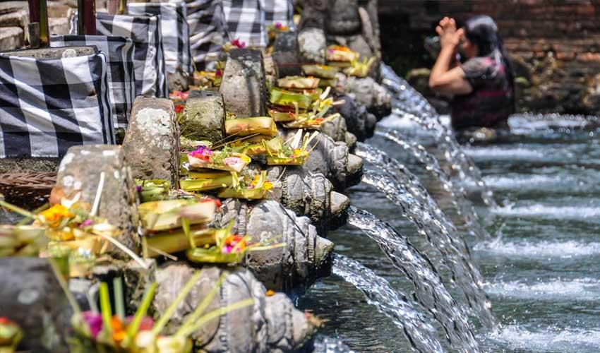 indonesie pas manquer femme en train de prier au temple Tirta Empul avec offrandes