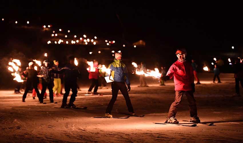 Descente aux flambeaux à Noël, pistes de ski enneigées, France
