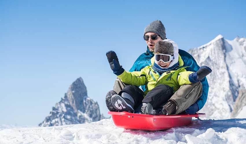 Père et fils faisant de la luge sur la neige à la montage - MMV