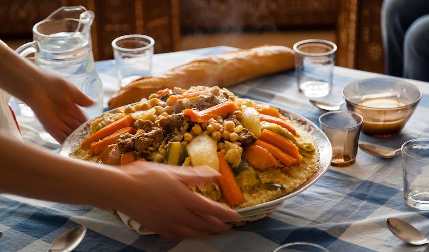 Une femme sert un couscous.