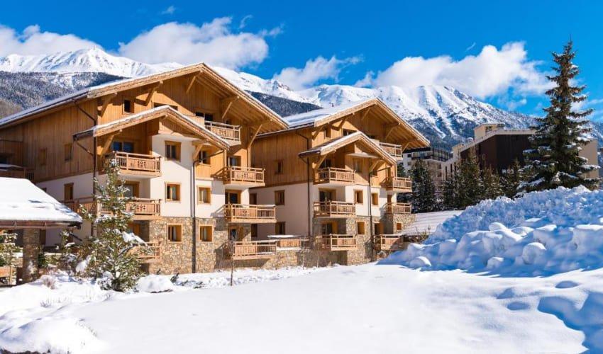 Vue extérieure de la résidence Le Hameau du Rocher Blanc, un hébergement Skissim Premium à Serre Chevalier